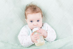 Sweet baby with big blue eyes drinking milk Stock Photography