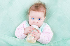 Sweet baby with big blue eyes drinking milk Stock Image
