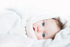 Sweet baby with blue eyes playing peek-a-boo Royalty Free Stock Images
