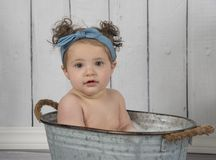 Sweet baby in blue headband sits in washtub royalty free stock photos