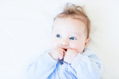 Sweet baby in a blue knitted sweater sucking on its hand Royalty Free Stock Photo