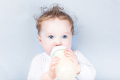 Sweet baby in a blue sweater drinking milk Royalty Free Stock Photography