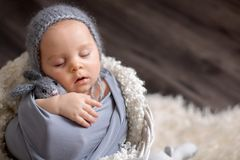 Sweet baby boy in basket, holding and hugging teddy bear, peacefully sleeping. Wrapped in grey scarf stock photo