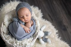 Sweet baby boy in basket, holding and hugging teddy bear, peacefully sleeping. Wrapped in grey scarf royalty free stock photography