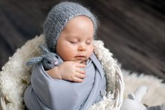 Sweet baby boy in basket, holding and hugging teddy bear, peacefully sleeping. Wrapped in grey scarf royalty free stock photo