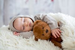 Sweet baby boy in bear overall, sleeping in bed with teddy bear. Stuffed toys, winter landscape behind him stock photos