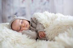 Sweet baby boy in bear overall, sleeping in bed with teddy bear. Stuffed toys, winter landscape behind him royalty free stock photos