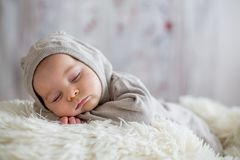 Sweet baby boy in bear overall, sleeping in bed with teddy bear. Stuffed toys, winter landscape behind him stock photography