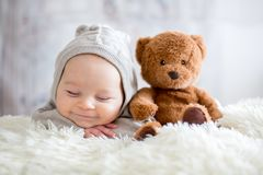 Sweet baby boy in bear overall, sleeping in bed with teddy bear Royalty Free Stock Image