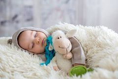 Sweet baby boy in bear overall, sleeping in bed with teddy bear. Stuffed toys, winter landscape behind him stock image