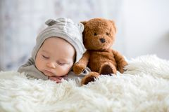 Sweet baby boy in bear overall, sleeping in bed with teddy bear. Stuffed toys, winter landscape behind him royalty free stock photography