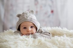 Sweet baby boy in bear overall, sleeping in bed with teddy bear. Stuffed toys, winter landscape behind him stock photo