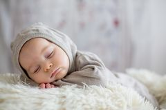 Sweet baby boy in bear overall, sleeping in bed with teddy bear. Stuffed toys, winter landscape behind him royalty free stock images