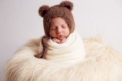 Sweet baby boy in bear overall, sleeping in bed with teddy bear stuffed toys, winter landscape behind him.  stock images