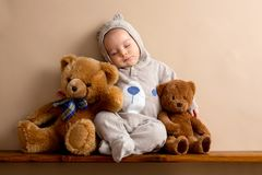 Sweet baby boy in bear overall, sleeping on a shelf with teddy b. Ears stuffed toys. Shot in studio on creamy background, shot from above stock photography
