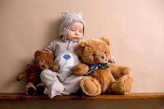 Sweet baby boy in bear overall, sleeping on a shelf with teddy b. Ears stuffed toys. Shot in studio on creamy background, shot from above stock photo