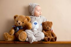 Sweet baby boy in bear overall, sleeping on a shelf with teddy b. Ears stuffed toys. Shot in studio on creamy background, shot from above stock image