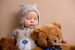 Sweet baby boy in bear overall, sleeping on a shelf with teddy b. Ears stuffed toys. Shot in studio on creamy background, shot from above royalty free stock photo