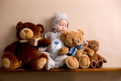 Sweet baby boy in bear overall, sleeping on a shelf with teddy b. Ears stuffed toys. Shot in studio on creamy background, shot from above royalty free stock images