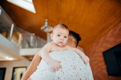 Baby boy on father`s shoulder. Sweet baby boy on daddy shoulder, father talking on phone Royalty Free Stock Image