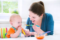 Sweet baby boy eating his first solid food with his mother. Young attractive mother feeding her cute baby son, giving him his first solid food, healthy vegetable Royalty Free Stock Photography