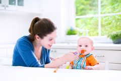 Sweet baby boy eating his first solid food witn hi. Young attractive mother feeding her cute baby son, giving him his first solid food, healthy vegetable pure Royalty Free Stock Image