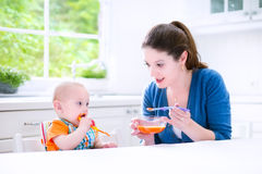 Sweet baby boy eating his first solid food. Young attractive mother feeding her cute baby son, giving him his first solid food, healthy vegetable pure from Royalty Free Stock Images