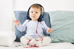 Sweet baby boy listening music at headphones in conducting posit stock images