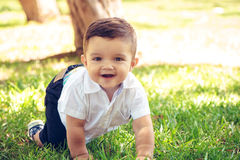 Sweet baby boy sitting in a autumn park stock photo