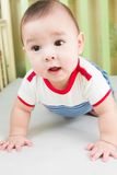 Sweet baby boy in striped clothes. In the cot stock photography