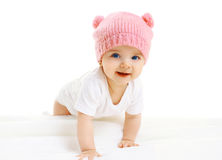 Sweet baby crawls in the pink knitted hat stock photo