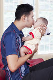 Sweet baby with dad on sofa at home Stock Image