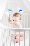 Sweet baby in a diaper holding a toy and sitting in its crib Stock Photography