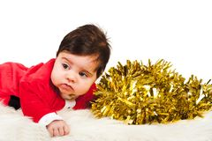Sweet baby dress as santa looking away with golden tinsel Royalty Free Stock Photos