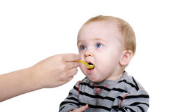 Sweet Baby Eating. Cute baby being feed rice cereal with a yellow spoon Stock Photography