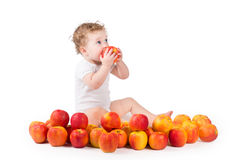 Sweet baby eating a red apple Royalty Free Stock Photos