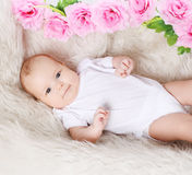 Sweet baby and flowers on the bed Stock Images