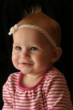 Sweet Baby Girl. Portrait of smiling 7 month old baby girl in a pink top and white hair bow Stock Image