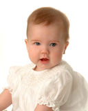 Sweet Baby Girl. Closeup of baby in white dress on white background Stock Photo
