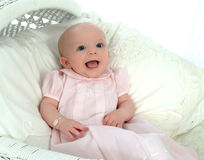 Sweet Baby Girl in Bassinet. Smiling baby girl in bassinet with pink dress Stock Image