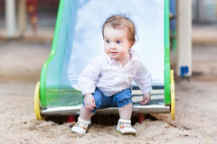 Sweet baby girl with blue eyes playing on slide Royalty Free Stock Photography