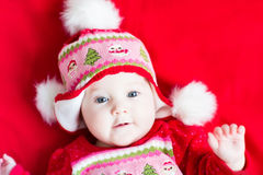 Sweet baby girl in a Christmas knitted dress and hat Stock Photos