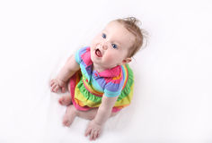 Sweet baby girl in colorful dress sitting on white blanket Royalty Free Stock Photos
