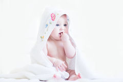 Sweet baby girl in a cross-stitched handmade towel Stock Photos