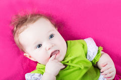 Sweet baby girl in a green dress on a pink blanket Stock Photos