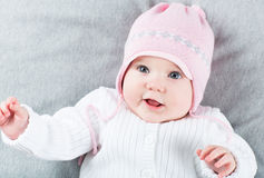 Sweet baby girl on a grey blanket wearing a pink hat. Sweet little baby girl on a grey blanket wearing a pink hat royalty free stock photo