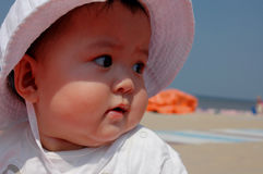Sweet baby girl with hat. Sitting on the beach Royalty Free Stock Photo