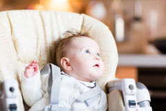 Sweet baby girl in a high chair waiting for dinner Royalty Free Stock Photography