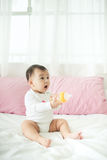 Sweet baby girl holding water bottle at home Royalty Free Stock Image