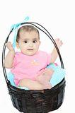 Sweet baby girl/kid sitting in a  wooden basket. Royalty Free Stock Image